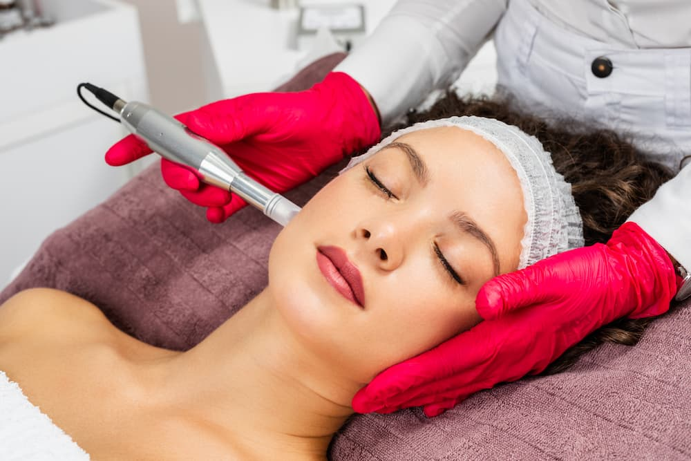 Woman lying down with eyes closed getting a microneedling procedure done